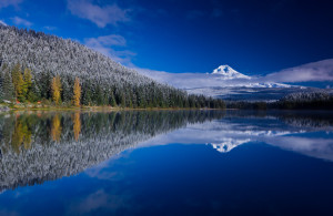 Scenic view of snow capped Mount Hood and its reflection in lake in foreground.
